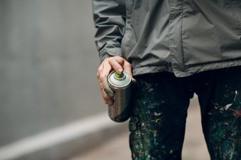 person holding spray paint can