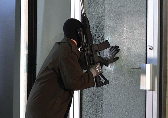 person with gun breaking door